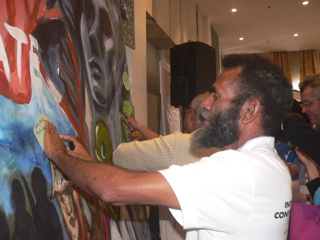"Patrick Yepe Lombaia of Papua New Guinea sticks a ""wish leaf"" on the IPCM mural (Photo by D.Ayroso/Bulatlat.com)"