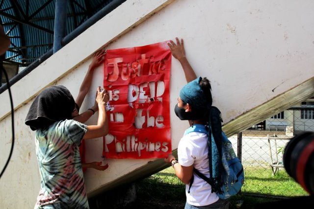 """Protesters paint the words """"Justice is dead in the Philippines"""" during the funeral caravan of Emerito Samarca."""