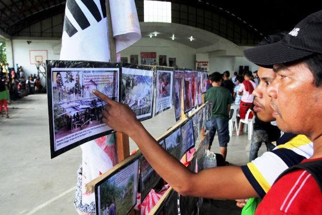 """People who visited the wake of Alcadev director Emerito Samarca look at the photos of the """"Lianga Massacre"""" displayed in the Capitol Gym in Butuan City."""