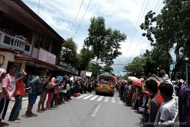 Mourners raised their fists as they lined up at the Lianga town proper (Photo courtesy of Manila Today)