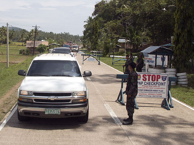 The funeral caravan from Tandag City had to pass through several police, army and paramilitary checkpoints. (Photo by Raymund Villanueva)