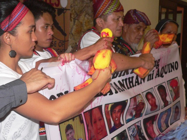 Indigenous leaders hold 'blood-soaked' yellow ribbons over images of victims of killings (Photo by D.Ayroso/Bulatlat.com)