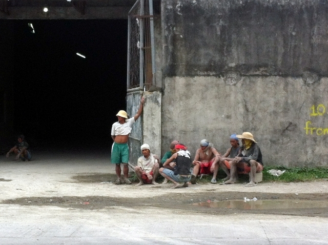 Workers covered with cement dust wait by a warehouse's gate to catch their breath and wait for their day's paltry wages. (Marasbaras, Tacloban City)