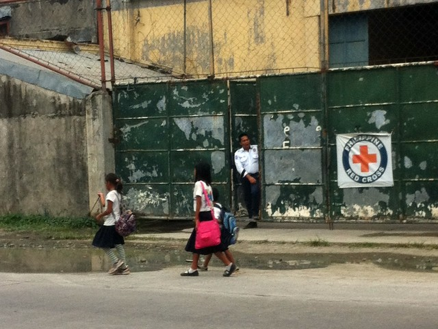Schoolchildren walk home from school, passing by a seemingly bored security personnel guarding a Red Cross warehouse now empty of relief items. (Marasbaras, Tacloban City)