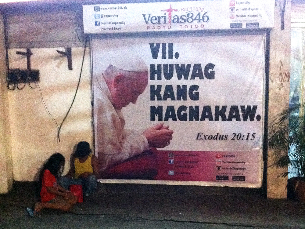 A homeless father and daughter take a break in front of an image that may just explain why there are many poor people in this country. (West Avenue corner EDSA, Quezon City)