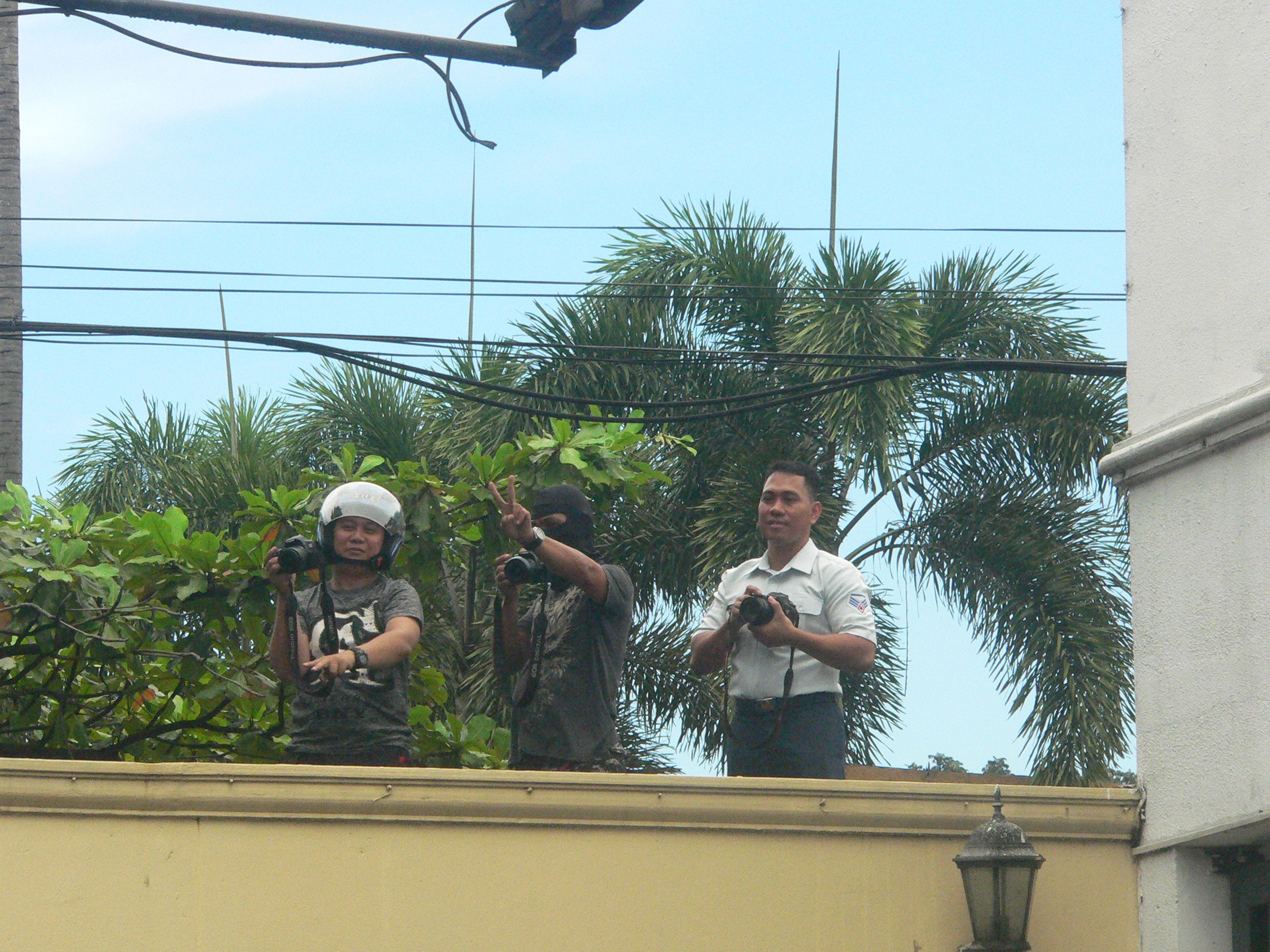 PEACE?  AFP personell, including one in a ski mask,  take photos of protesters over the Camp Aguinaldo wall (Photo by D.Ayroso/Bulatlat.com)