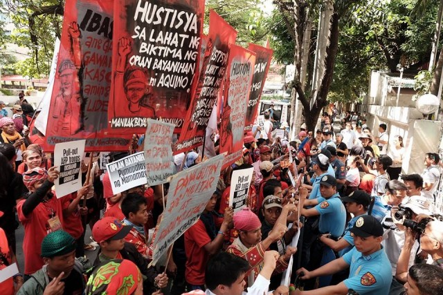 Protesters face anti-riot police men in front of the DOJ office in Manila (Photo by Manila Today)