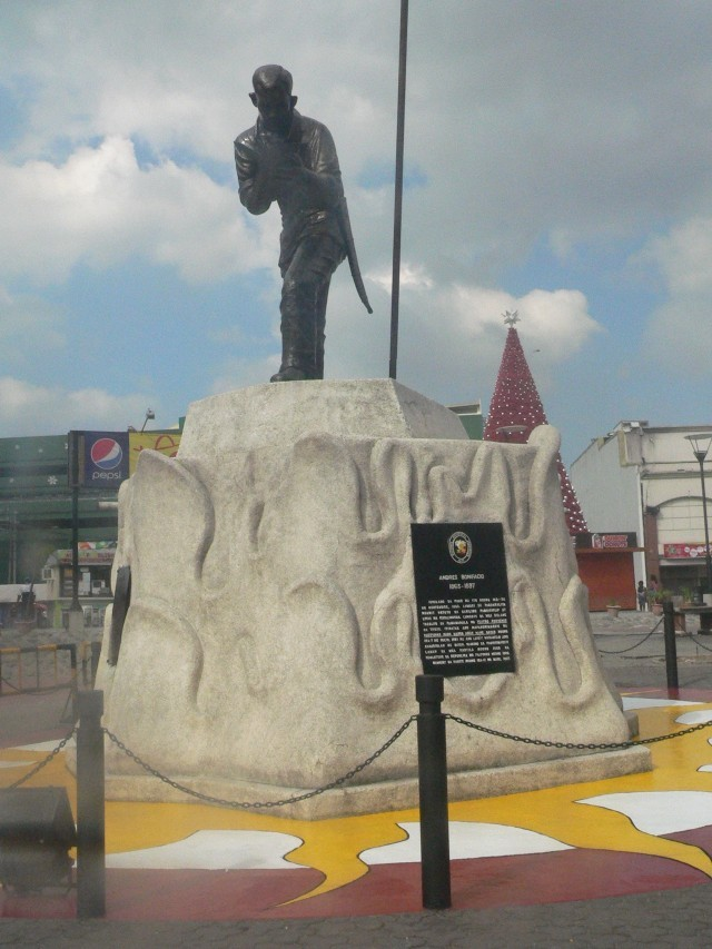 "BIRTHPLACE OF THE GREAT PLEBIAN. Bonifacio's monument stands in Tutuban, Divisoria, the general area where his family's home stood. Tutuban came from ""tubaan,"" the Tagalog word which means a place where they make tuba or coconut wine. From another angle, the monument is barely noticed, dwarfed by mall buildings and Christmas decors."