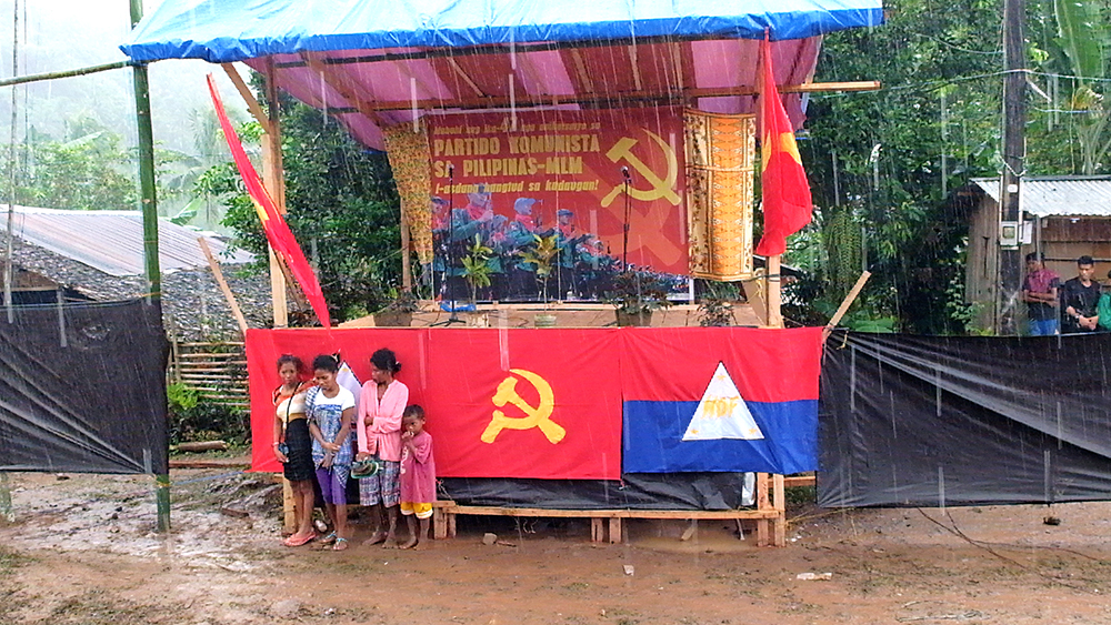 Attendees of the CPP's 47th anniversary celebrations take shelter as heavy rain poured before the program started. (Kitcharao, Agusan del Norte)