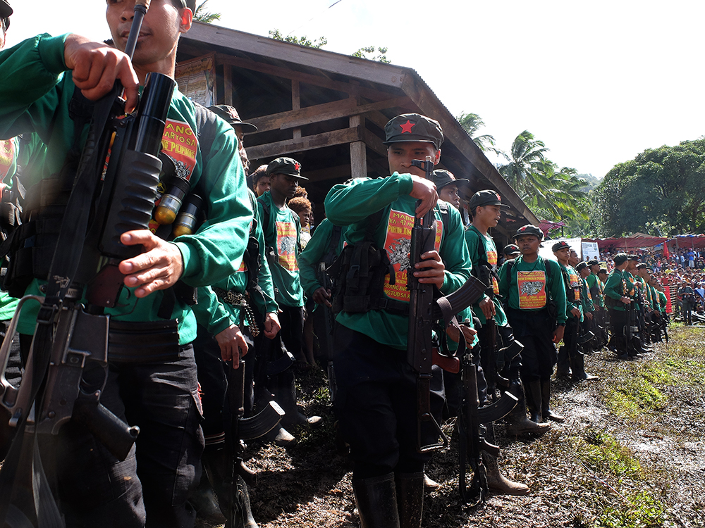 """A company of New People's Army guerillas gets ready to start the Communist Party of the Philippines' 47th anniversary program after leading the singing of the communist hymn """"Ang Internasyunal."""" (Kitcharao, Agusan del Norte)"""
