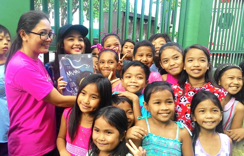 Gabriela Women's Party second nominee Arlene Brosas and child actress Andrea Brillantes poses with the children of barangay UP Campus in Quezon City after the read-along activity. (Photo by A. Umil/ Bulatlat)