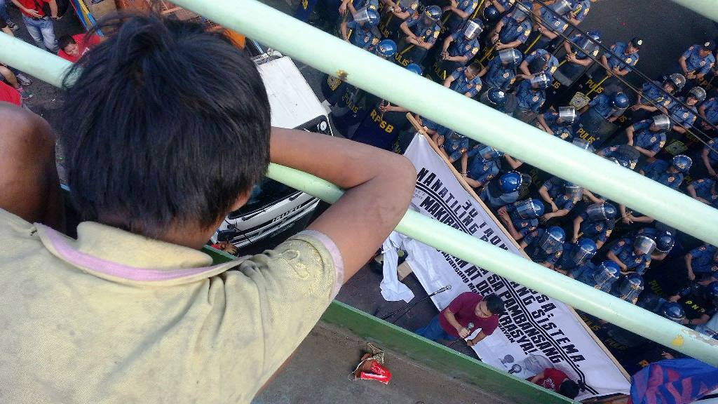 A street kid listens to the program during the 30th Edsa People Power 1 protest on Feb. 25.  commemoration