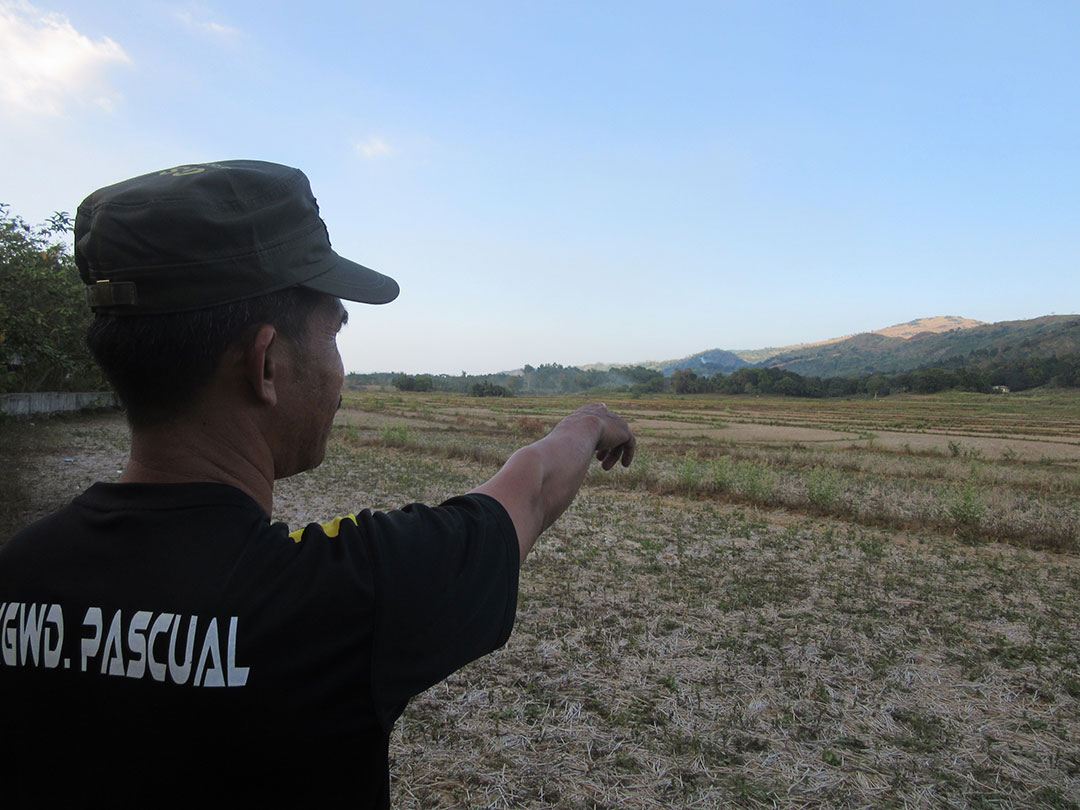 Jimmy Pascual points to the site of the solar project in Macabud village. (Photo by Miko Mendizabal / Bulatlat)