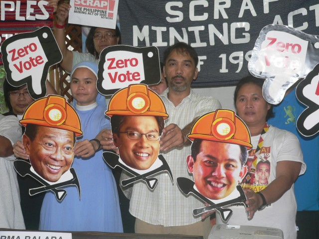 "Conveners of Scrap the Mining Act Network hold images of ""pro-mining candidates,"" Vice President Jejomar Binay, former Secretary Mar Roxas, and Congressman Martin Romualdez. (Photo by D.Ayroso/Bulatlat.com)"