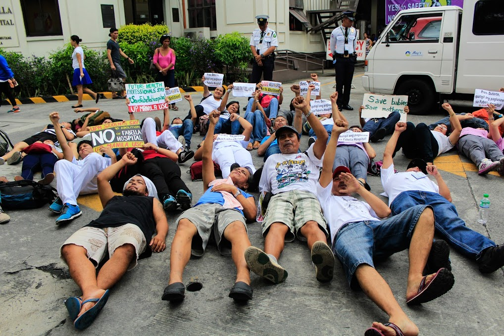 Protesters stage a die-in outside Fabella Hospital. (Photo by K.A. Macalalad/ Bulatlat)