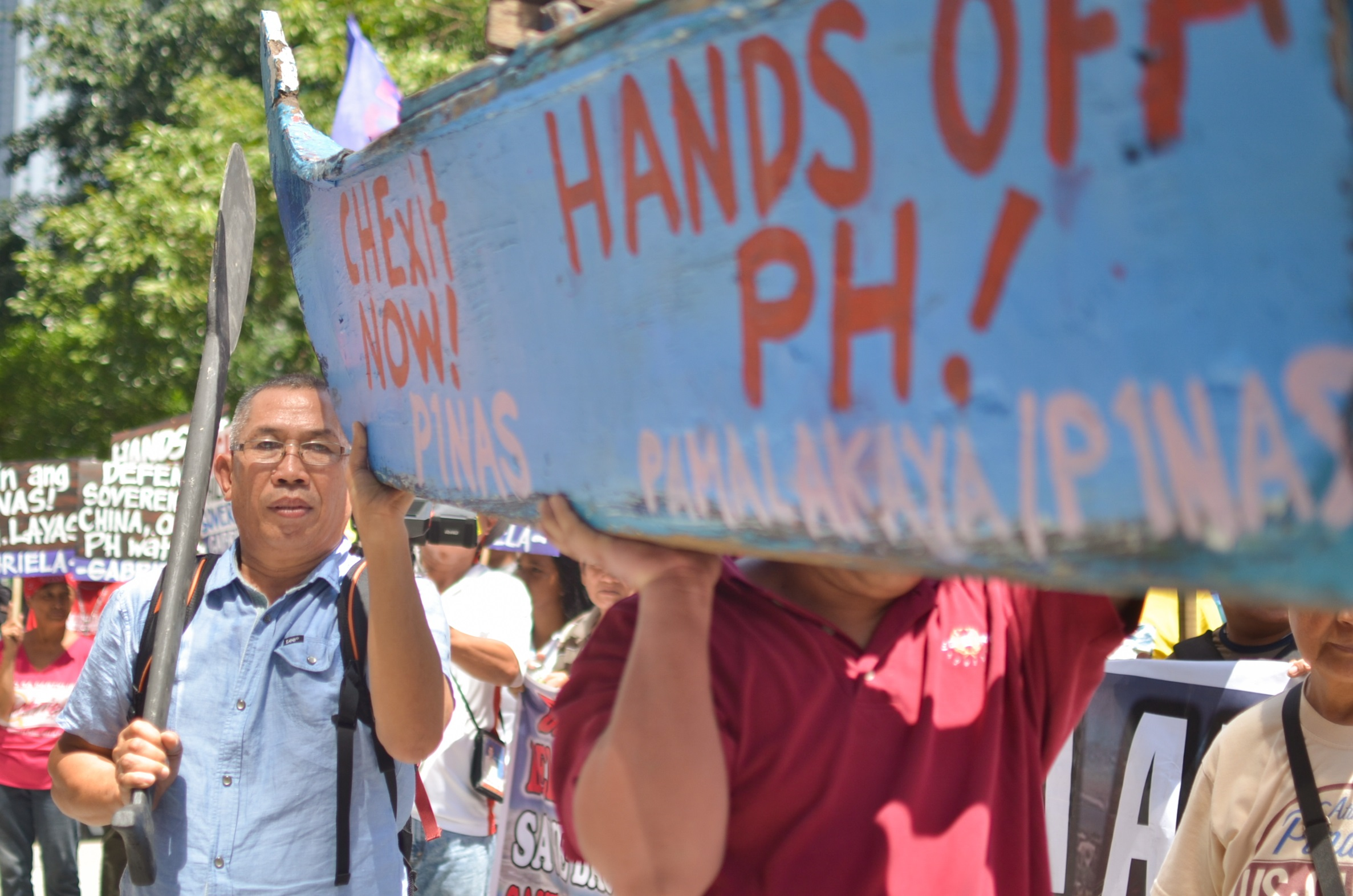 BULATLAT FILE PHOTO. Pamalakaya vice chairperson Salvador France carries a symbolic boat along with other fisherfolk at the July 12 protest in front of the Chinese Consulate in Makati City (Photo by Carlo Manalansan/Bulatlat)