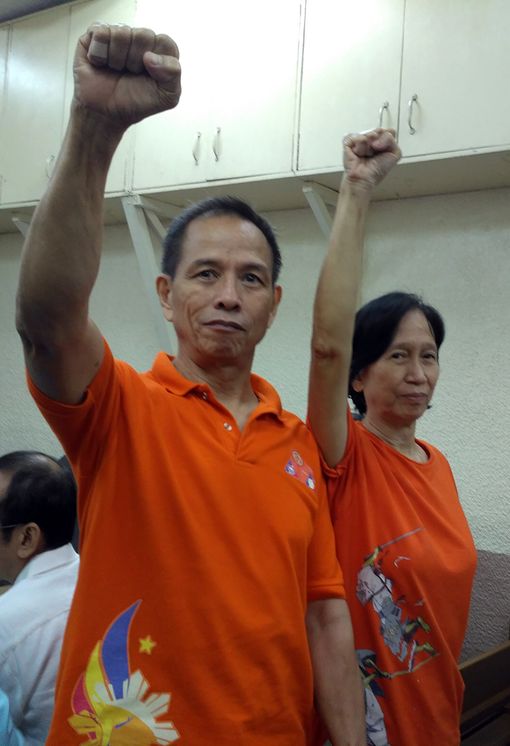 NDFP consultants Benito Tiamzon and Wilma Tiamzon raise their clenched fists before the start of the Aug. 10 hearing at a Manila local court. (Photo by Ronalyn V. Olea)