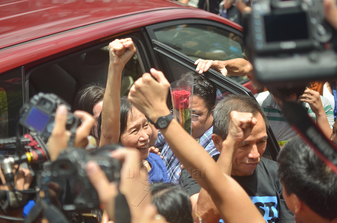 Supporters and members of the media greet Wilma and Benito Tiamzon as they walk out of Camp Crame this morning. (Photo by Loi Manalansan / Bulatlat)