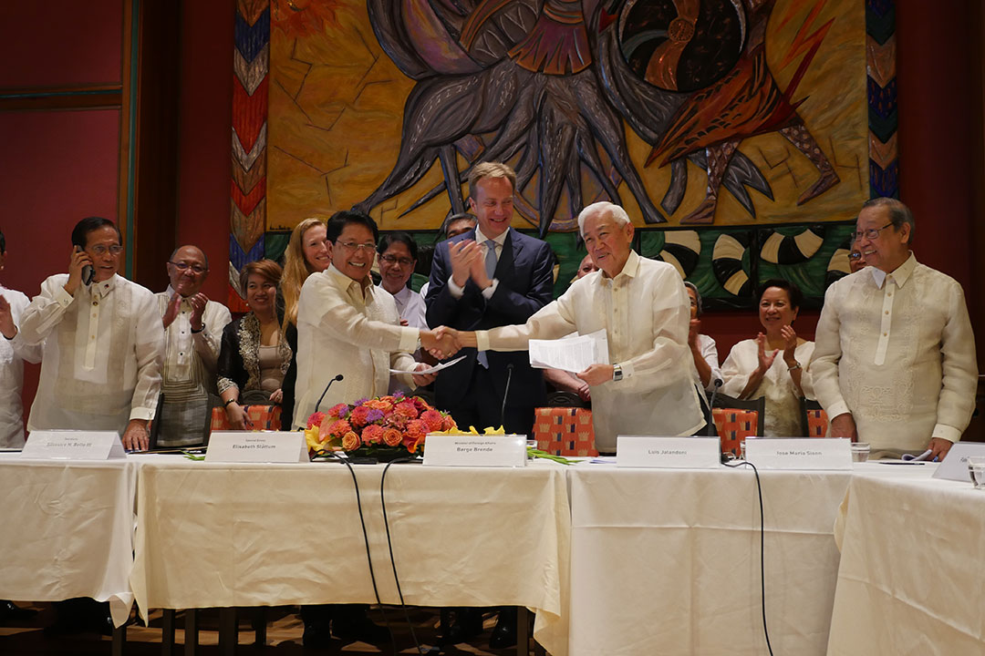GRP Peace Panel Chairperson Silvestre Bello III and NDFP Peace Panel Chairperson Luis Jalandoni shake hands during the signing of the joint statement in the first round of formal talks in Oslo, Norway. (Photo by Kodao Productions)