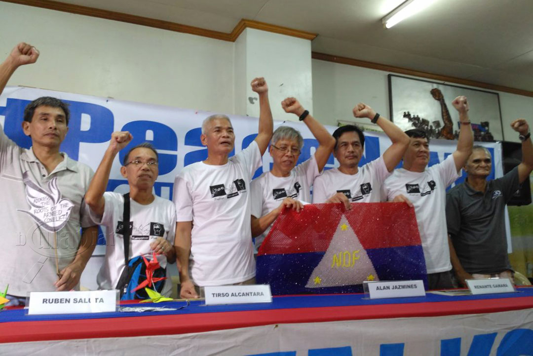 (L-R) NDFP consultants Kennedy Bangibang, Ruben Saluta, Tirso Alcantara, Alan Jazmines, Renante Gamara, Ernesto Lorenzo and Jaime Soledad raise their clenched fists as they are welcomed by supporters, Aug. 17. (Photo by Ronalyn V. Olea / Bulatlat)