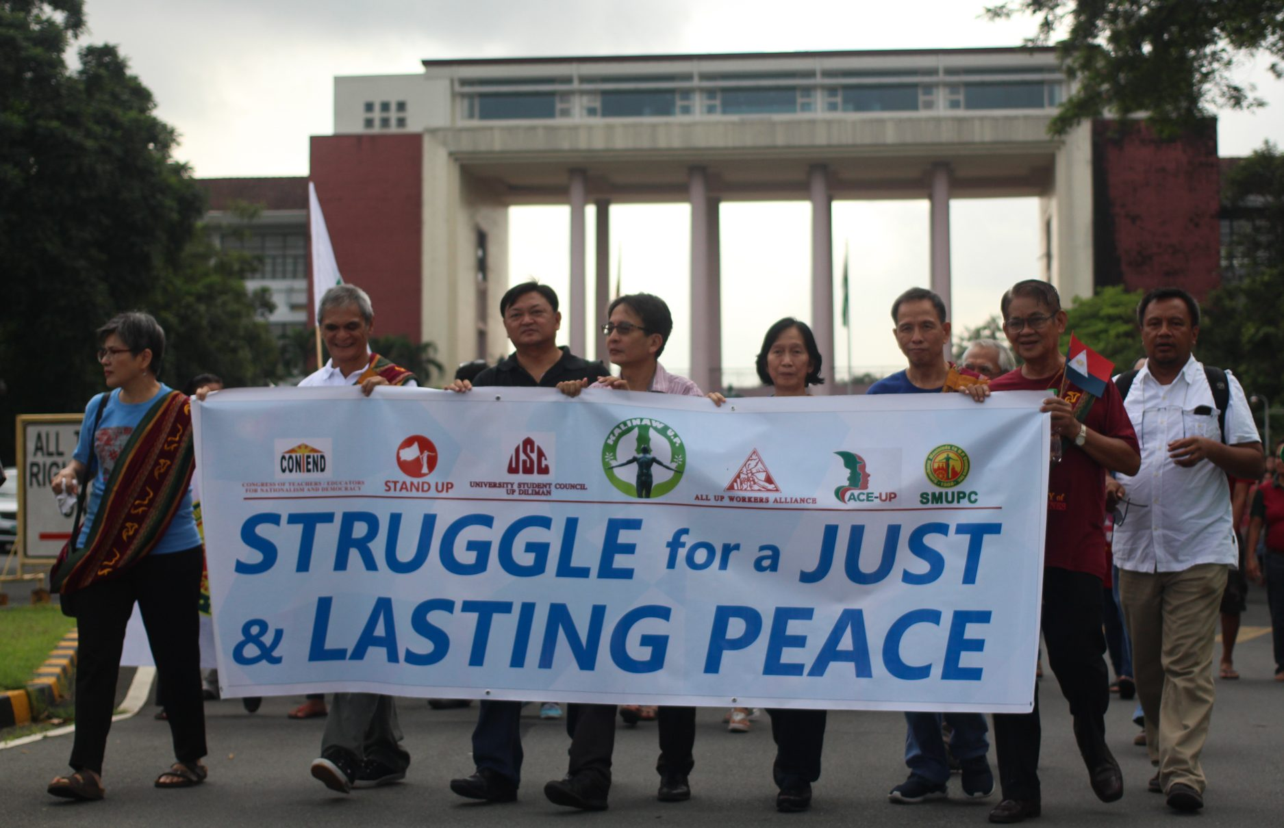 L-R: Dr. Carol Araullo of Bayan. NDFP peace consultant Jaime Soledad, UP Vice Chancellor for Community Affairs Nestor Castro and Chancellor Michael Tan, Wilma and Benito Tiamzon, Rafael Baylosis, Randy Malayao, join in the march towards the Diliman Commune marker (Photo by Gino Estella/Bulatlat)