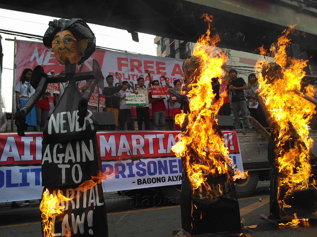 "Effigies of Imelda Marcos, Ferdinand ""Bongbong"" Marcos Jr. and Imee Marcos are set on fire during a protest commemorating the 44th anniversary of the declaration of martial law. (Photo by Ronalyn V. Olea/ Bulatlat)"