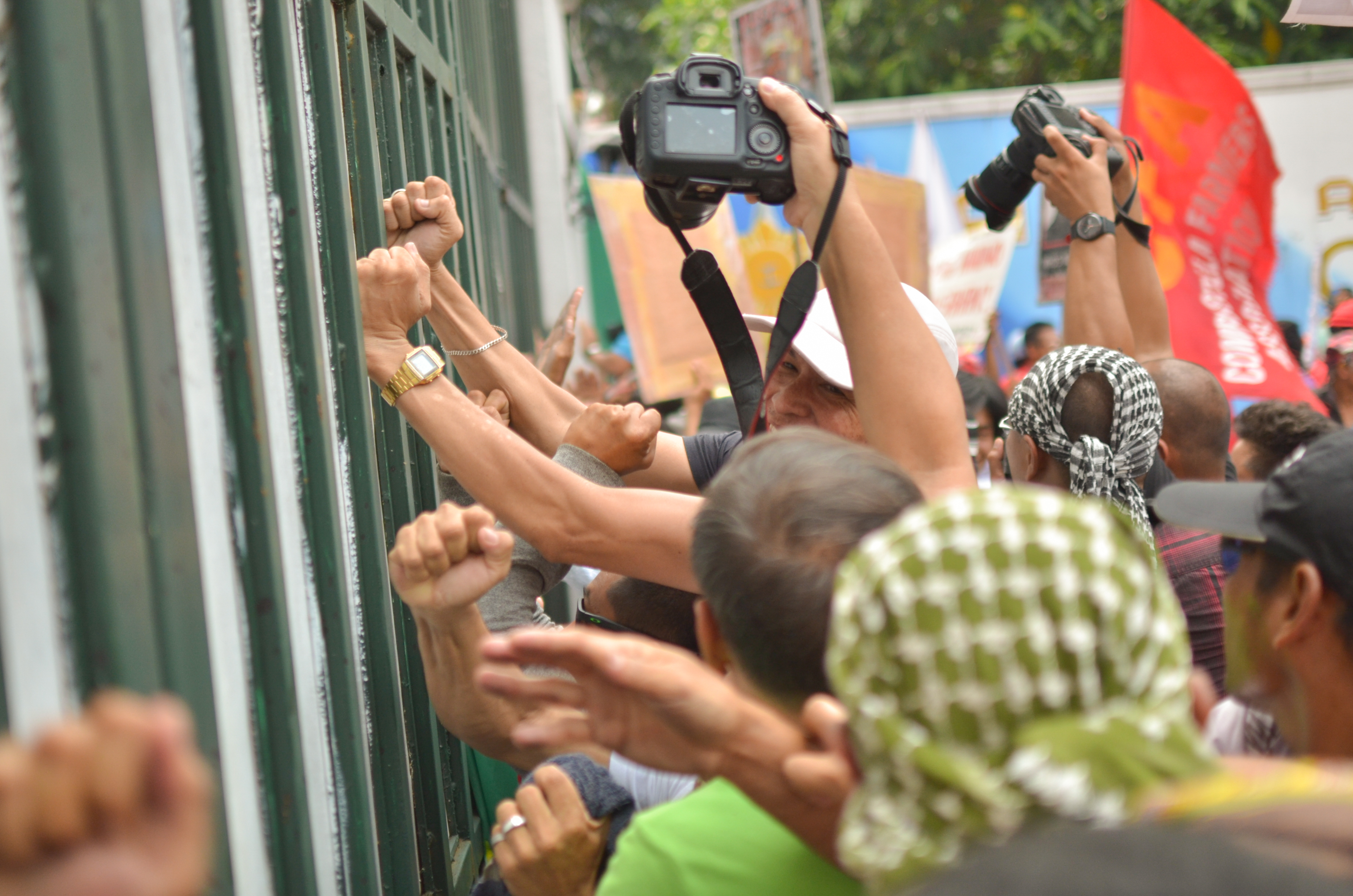 'BANGING ON THE BUTCHERS' GATE.' Protesters vent their ire on the iron sheet-covered gates of Camp Aguinaldo. (Photo by Carlo Manalansan/Bulatlat)
