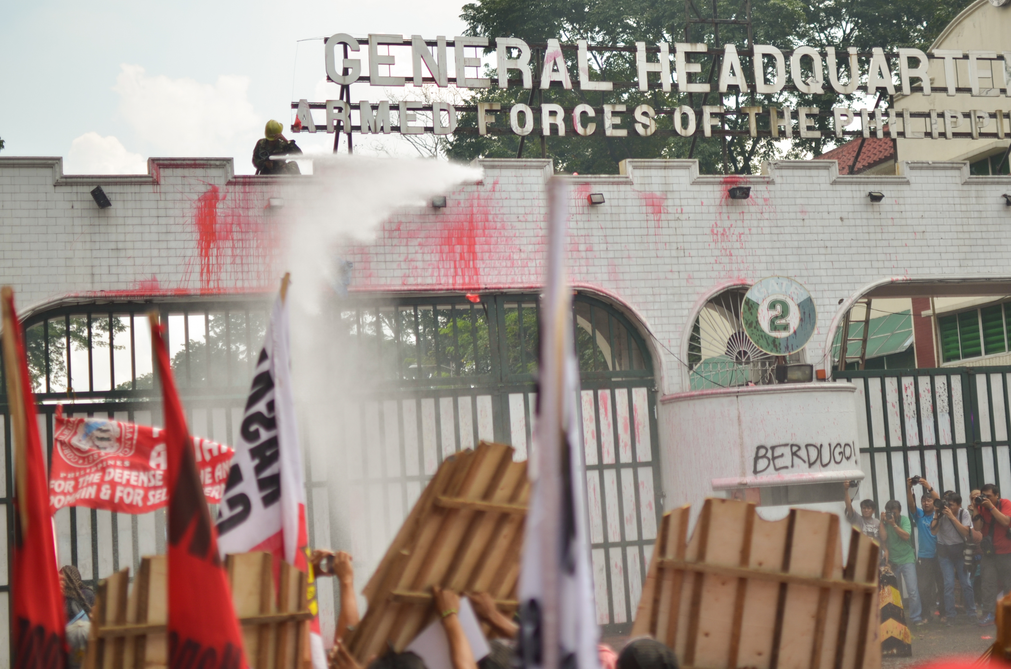 Protesters hurled red paint bombs on Camp Aguinaldo's gates, to depict the killings of activists by suspected soldiers and AFP-backed paramilitary groups. As soon paint smeared the gates, the AFP water cannons opened fired.(Photo by Carlo Manalansan/Bulatlat)