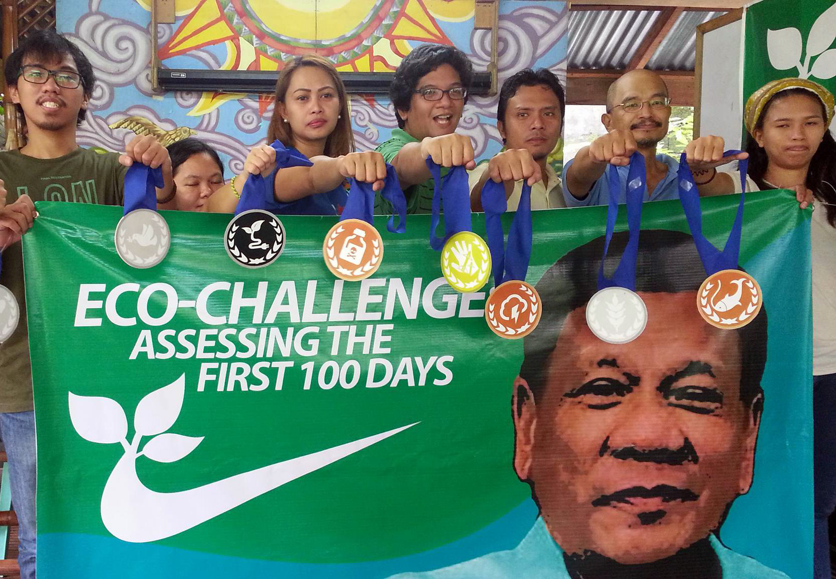"Representatives of groups under the Eco-Challenge Coalition hold ""medals"" garnered by the Duterte administration in its first 100 days (Photo courtesy of Enteng Bautista/Bulatlat)"