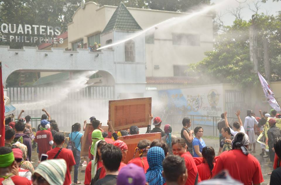 Drenched protesters stayed their ground amid the water cannon blasts by AFP personnel at the gate of Camp Aguinaldo. (Photo by Carlo Manalansan/Bulatlat)
