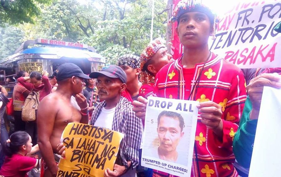 "Right: Datu Jimboy Mandagit holds a picture of Dominiciano Muya, a Salugpungan staff who had been detained since 2014. Mandagit himself had reported being branded as an ""NPA"" and hunted by soldiers and paramilitary men in his community in San Fernando, Bukidnon. (Photo by Kilab Multimedia)"
