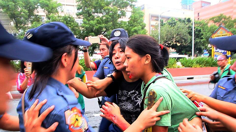 Injured Nicole Soria (in green shirt) being arrested by police women even as her companions were bringing her to the hospital (Photo by Kodao Productions)