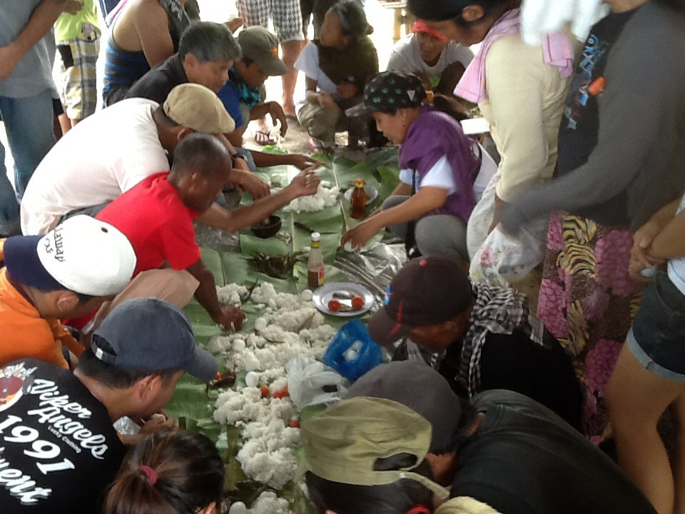 TASTE OF VICTORY. Luisita farmers and supporters share a solidarity lunch, which included eggplants, squash flowers and tomatoes harvested from a bungkalan area. (Photo by Dee Ayroso/Bulatlat)