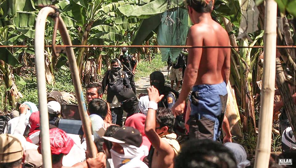 Masked armed men identified as private guards of the Lapanday Foods Corporation stand a short distance from farmer-beneficiaries on Dec. 12, 2016 (Photo by Kilab Multimedia)