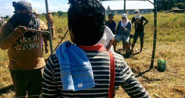 THREATS. Ambala chairperson Florida Sibayan (only back shown) confronts one of the thugs ordered by a Texas village chief to harass farm workers in Mapalacsiao village, Tarlac City (Photo courtesy of Luisita Watch)