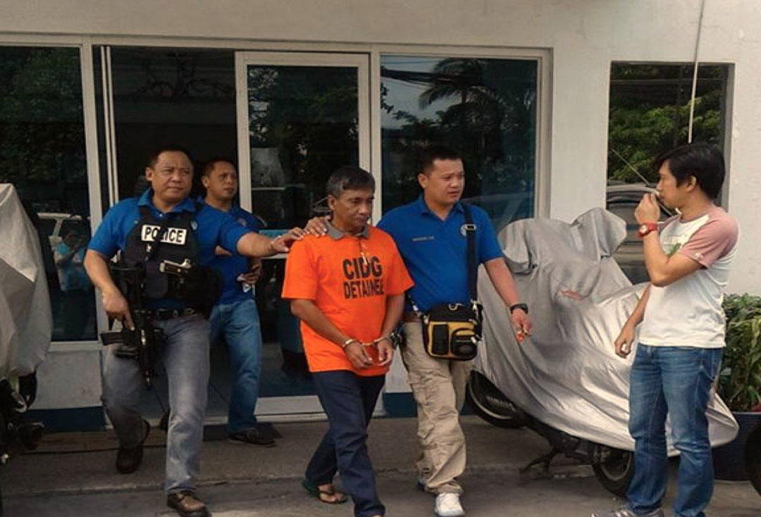 Ferdinand Castillo (in orange shirt) is escorted by elements of the CIDG. (Photo courtesy of Bayan-Metro Manila)
