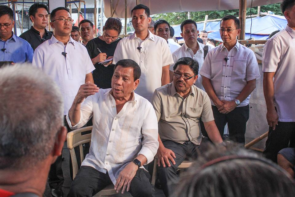 "FILE PHOTO: President Duterte (seated) speaks to Marbai and other farmer leaders, with DAR Secretary Rafael ""Ka Paeng"" Mariano (seated, right) inside the protest camp in Mendiola. (Photo by Kilab Multimedia)"