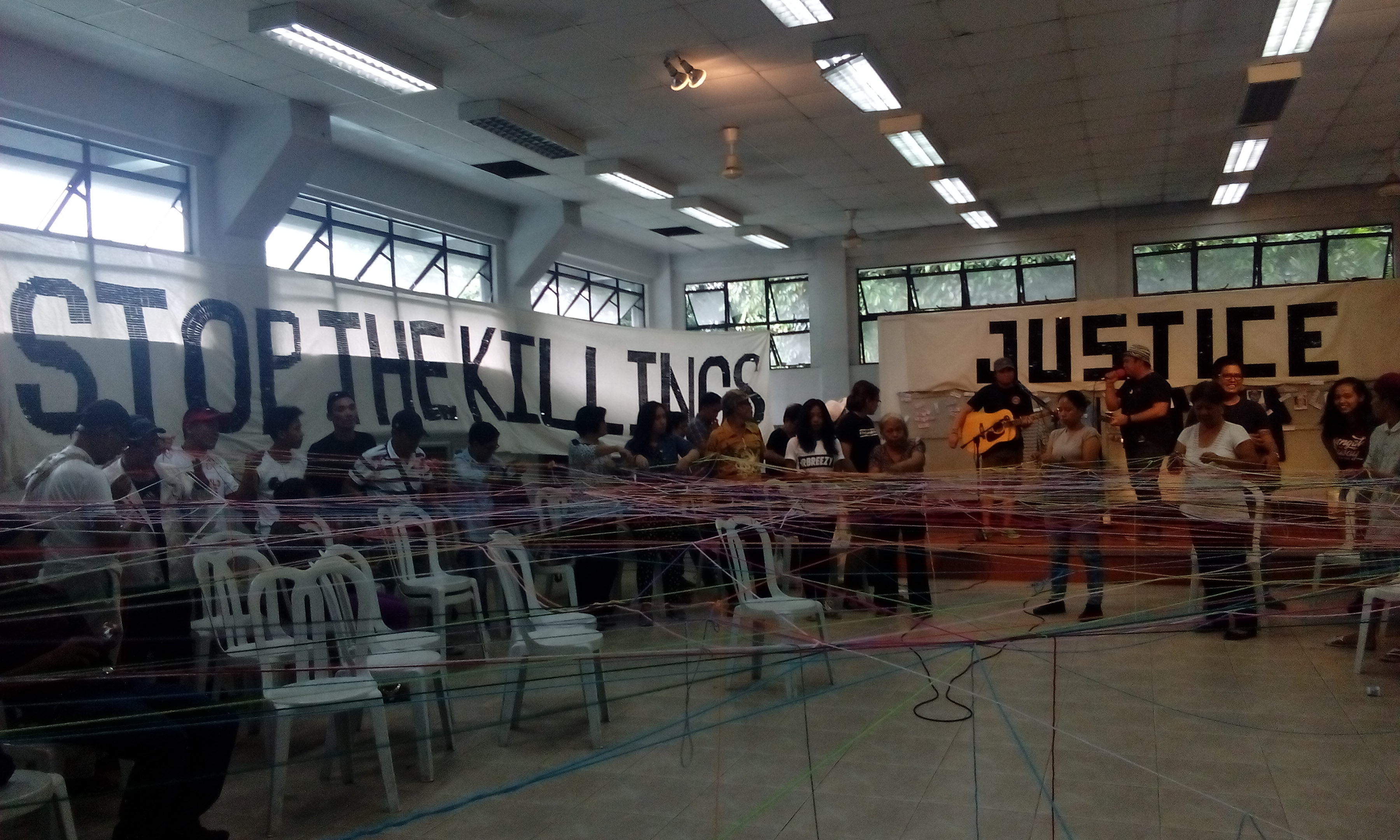 WEB OF LIFE. Former political prisoners, families of victims of enforced disappearance and political and drug-related killings 'spun' a web with colored yarn to symbolize their connection and united call for justice (Photo by Alab Mirasol Ayroso/Bulatlat)